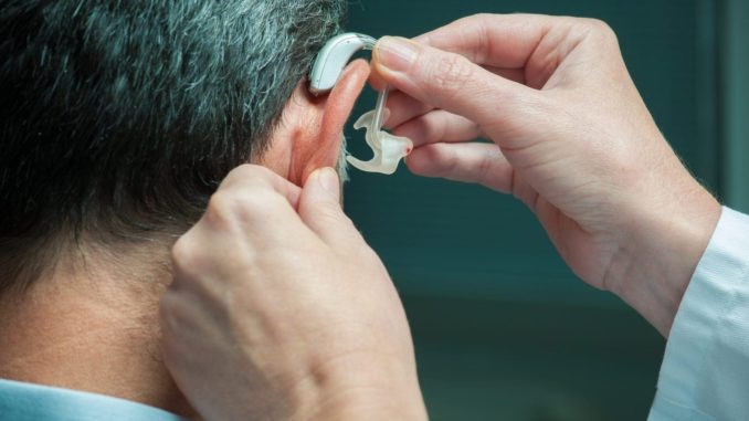 mengenakan alat bantu dengar